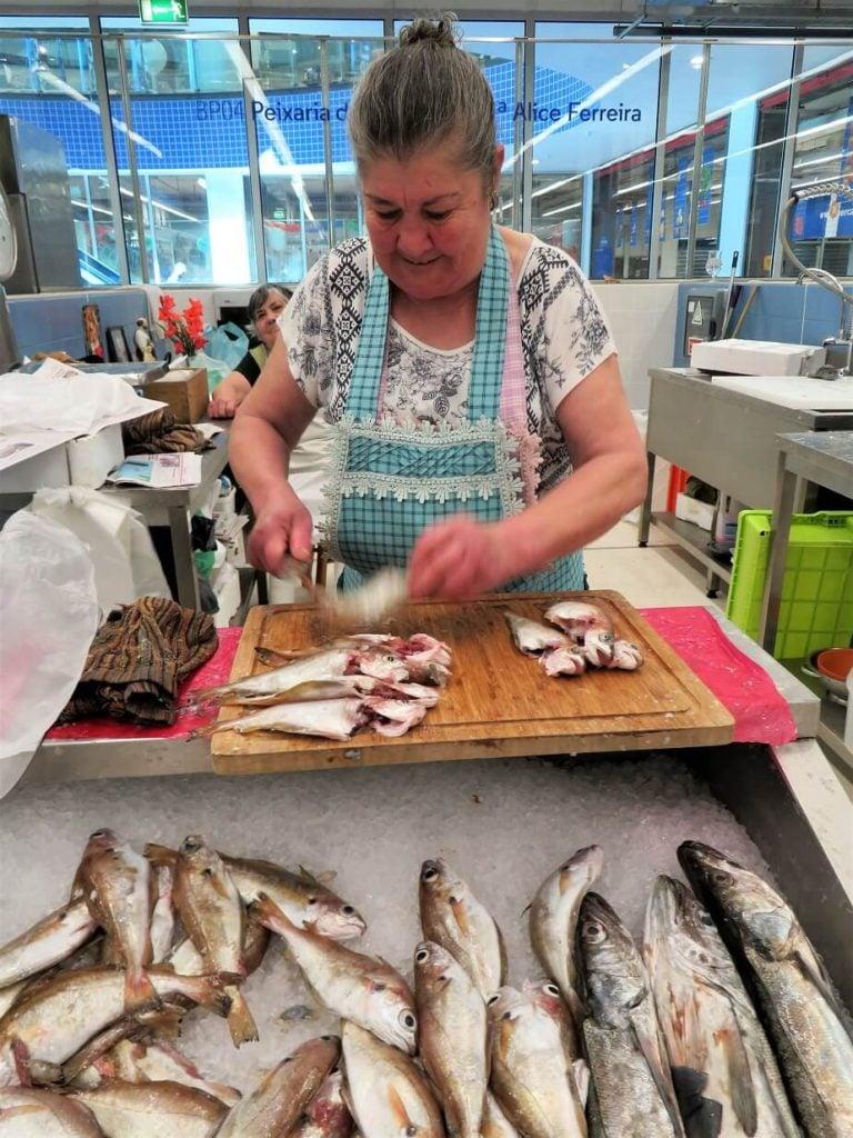 fish pate; fish vendor gutting fish at the market